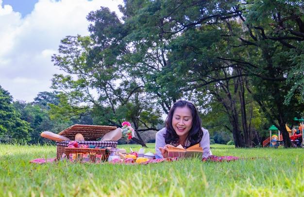 Молодая азиатская женщина расслабиться время в парке. Premium Фотографии