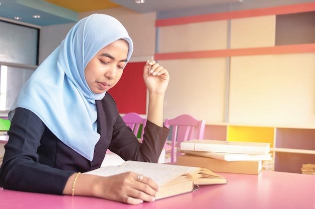 若い学生イスラムの女性。彼女は座って本を読んでいます。 Premium写真