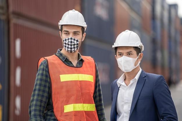 Бизнесмен и фабричные рабочие нося в медицинской маске и ткани безопасности на внешнем складе груза фабрики. Premium Фотографии