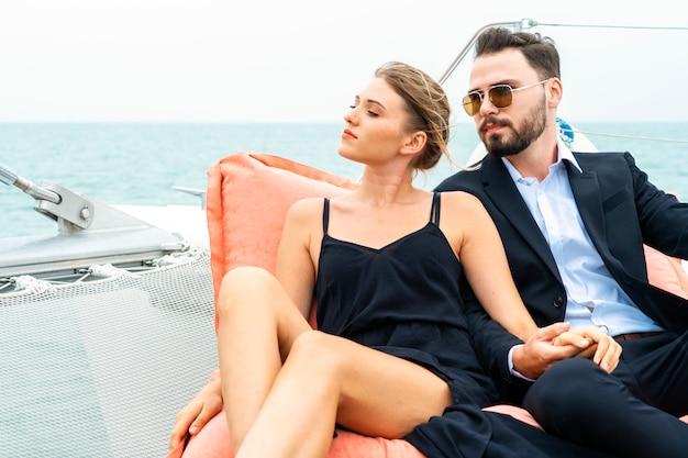 素敵なドレスとスイートの豪華でリラックスしたカップルの旅行者は、クルーズヨットの一部で豆の袋の上に座る。 Premium写真
