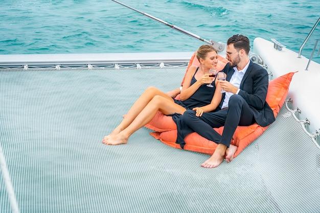 素敵なドレスとスイートの豪華でリラックスしたカップルの旅行者は、ビーンバッグの上に座り、クルーズヨットの一部でワインを飲みます。 Premium写真