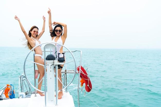 ビキニのセクシーな女の子が立っているとボートのヨットの上でドライバーの手のステアリングホイールとダンス Premium写真