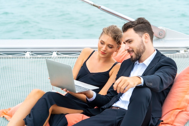 Роскошная расслабляющая пара путешественников в красивом платье и люксе сидит на бобовой сумке и смотрит на компьютер Premium Фотографии