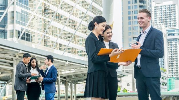 スマートシティの人々ビジネスのグループが屋外都市空間で会う Premium写真