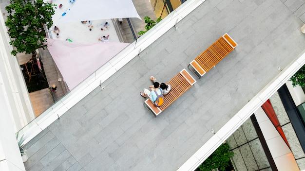 愛の男女は上からの眺めで歩行者通路で木製のベンチに座る Premium写真