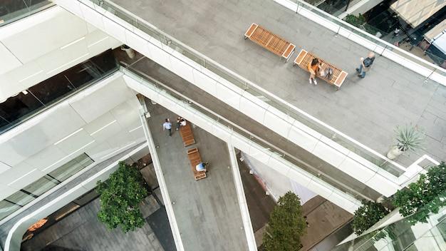 買い物袋を持つトップ空撮ファッション女性は歩道橋で木製のベンチに座っているスマートフォンを使用しています。 Premium写真