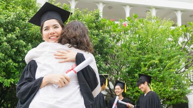 Девочка-студентка с выпускным платьем и шляпой обнимает родителя на церемонии поздравления. Premium Фотографии