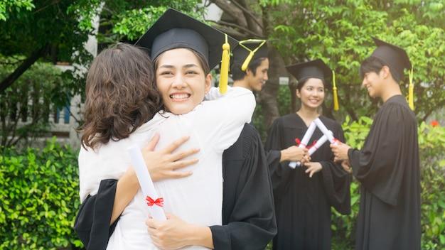 Девочка-студентка с выпускным платьем и шляпой обнимает родителя на церемонии поздравления Premium Фотографии
