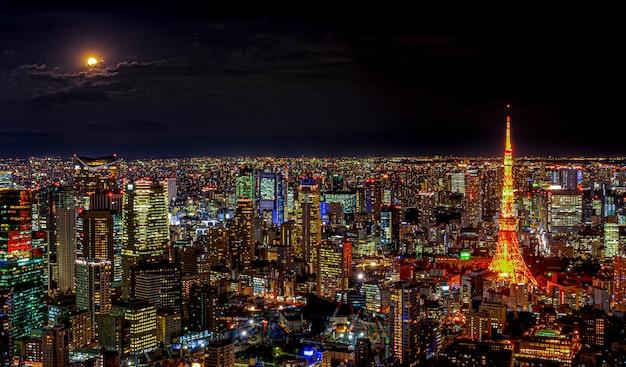 夜のスカイラインの下で建築建物の照明と東京の日本の満月と雲の光で近代的な都市のパノラマ。 Premium写真