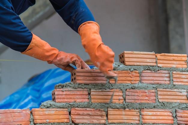 建設現場で赤レンガをインストールする労働者 Premium写真