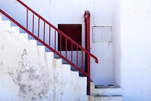 古い剥離白塗りの家とギリシャの赤い梯子 Premium写真