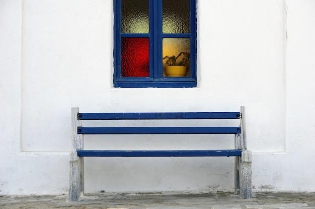 白い壁に美しい青い窓枠の下の青い木製ベンチ Premium写真