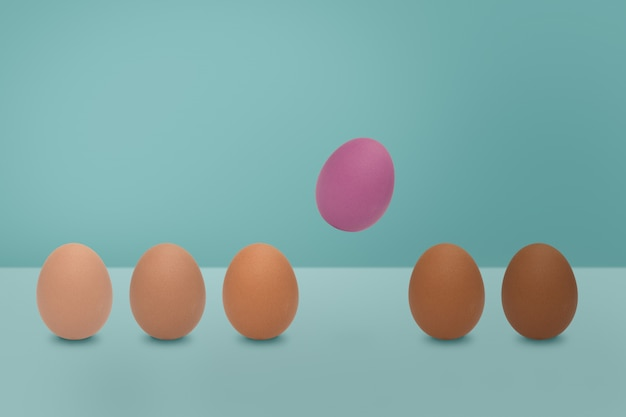 青い背景にピンクの卵と卵の色合いの色を飛んでいます。最小限のイースターの考え。 Premium写真