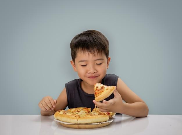 少年は木製のプレート上に伸びたホットチーズの溶融ピザを食べて幸せです Premium写真
