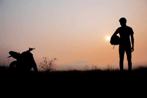 夕日とバイカーの男性。 Premium写真