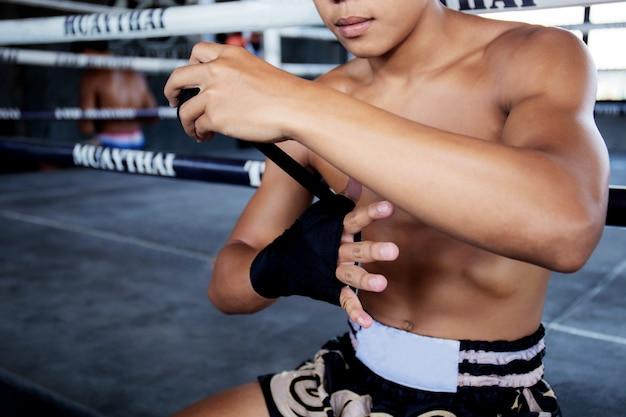 ボクサーの男性が手を包んでいます。 Premium写真