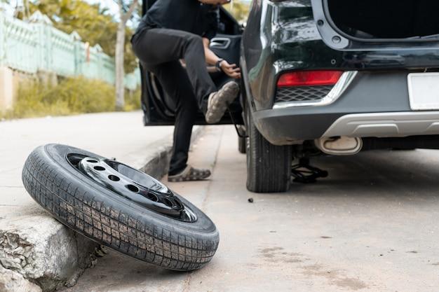 男性は道路脇のタイヤを変えている Premium写真