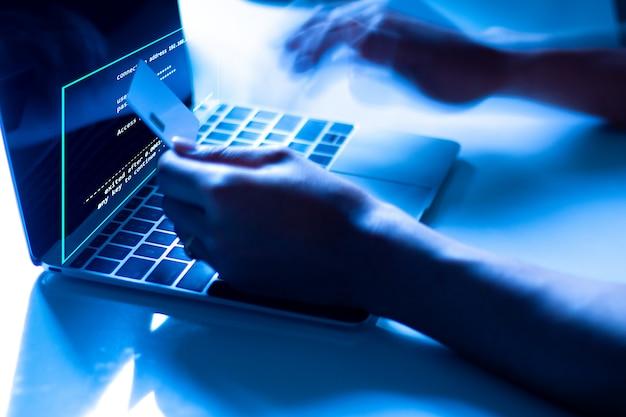 クレジットカードの盗難の概念ラップトップにクレジットカードを持っているハッカーはこれらのデータを使います Premium写真