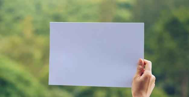 自然の背景に手でビジネスペーパーを表示します。 Premium写真