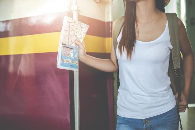 旅行者の若い女性がバックパックを見て鉄道駅で地図を保持します。観光の日。 Premium写真