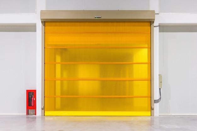 ローラーシャッタードアとコンクリートの床は、工業用の工場の建物内にある。 Premium写真