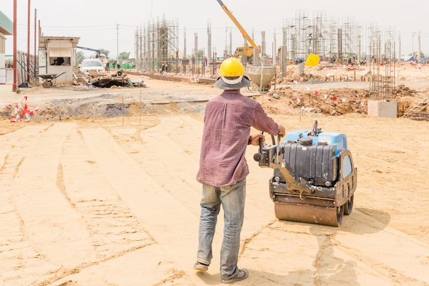 道路建設作業中の道路ローラー中の建設労働者。 Premium写真