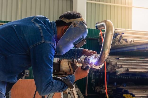 ティグ溶接機を使用して保護マスク溶接金属配管を持つ産業労働者 Premium写真
