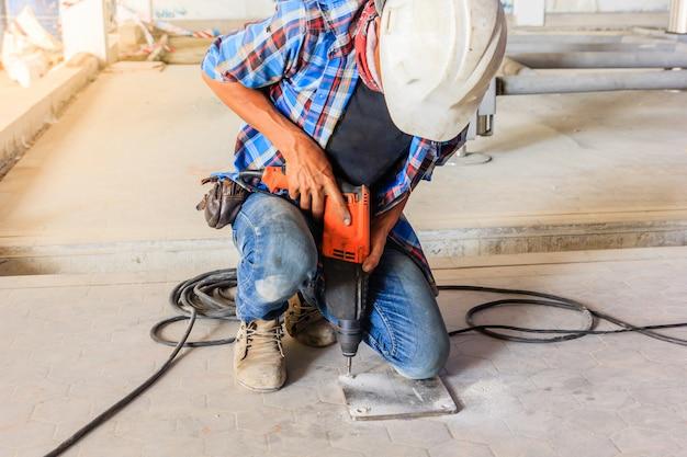 電気ドリルを使用して工事現場に鋼板を設置する建設作業員。 Premium写真