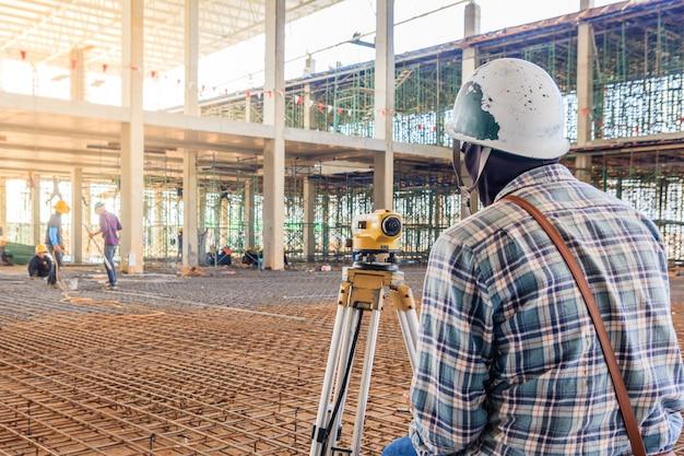 検査員は、工場建設現場でセオドライト装置で測定を行います。 Premium写真