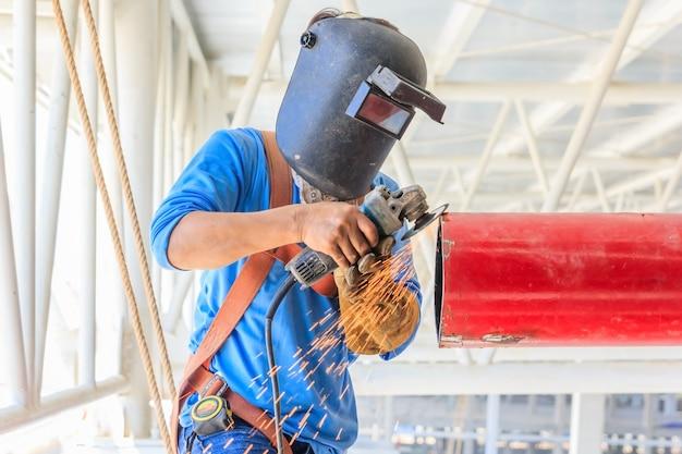 電気ホイール研削による鋼管を研削する重工業労働者 Premium写真