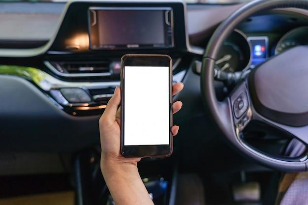 車の中で携帯電話を使用して女性ドライバーの手のクローズアップ Premium写真