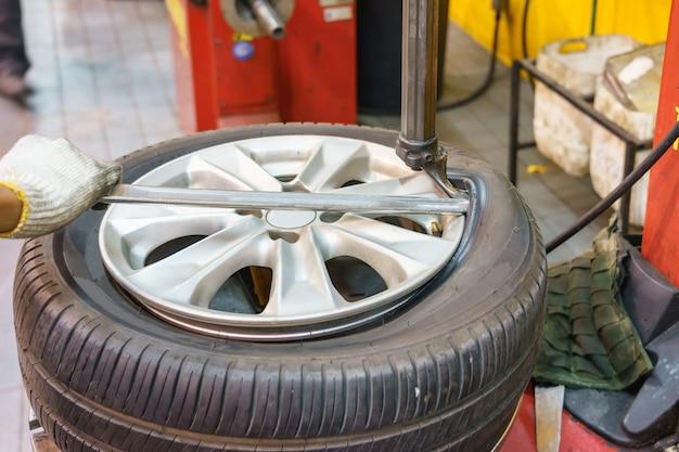 ワークショップで車のタイヤを変更するメカニックのクローズアップ Premium写真