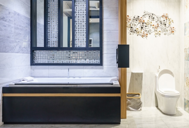 ミニマルなシャワーと照明、白いトイレ、洗面台、バスタブ付きのモダンなバスルームのインテリア Premium写真