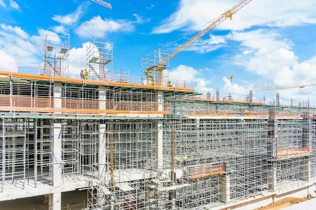 近代的な建物は建設中、金属製の足場と青い空 Premium写真