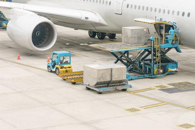 航空機への航空貨物の積込みプラットフォーム。飛行機に搭乗する前に準備ができているフライトチェックインサービスと機器のための食物。 Premium写真