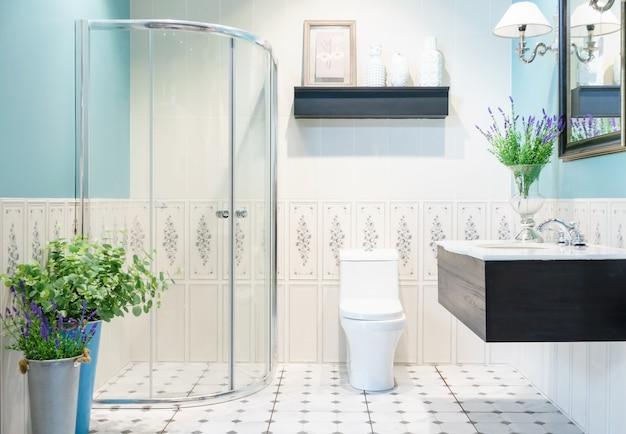 ガラス張りのシャワー、トイレ、シンク付きの明るいタイル付きのモダンな広々としたバスルーム。側面図 Premium写真