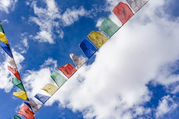 鮮やかな色でカラフルな仏教の祈りのフラグは青い空を背景にチベットの安全旅行のためのテールマンとして使用 Premium写真