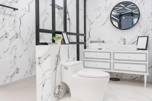 白い壁、ヴィンテージ家具、タオル、トイレ、洗面台付きのバスルームのインテリア Premium写真
