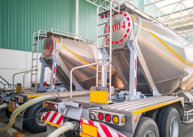 製造工場で貯蔵サイロに砂糖を積み込むタンカー貯蔵トラック。 Premium写真