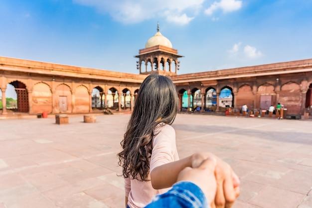 アジアの若い女性観光客は、インドのオールドデリーの赤いジャマモスクに男をリードします。一緒に旅行します。フォローしてください。 Premium写真