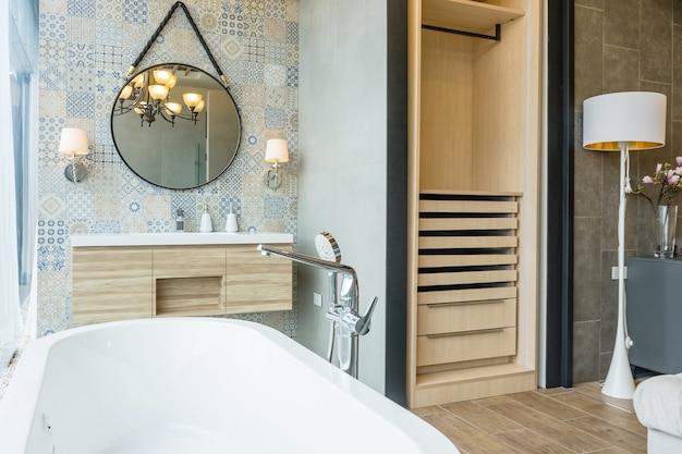 Белый интерьер ванной комнаты с мозаикой, белый и деревянный пол, овальная ванна, раковина и круглые зеркала Premium Фотографии