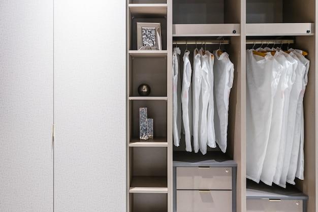 Современный деревянный шкаф с женской одеждой, висящей на рельсе в гардеробной в скандинавском стиле Premium Фотографии