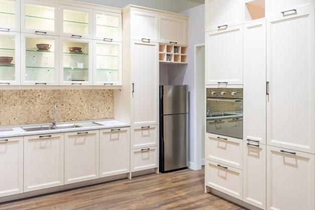高級マンションのステンレス製電化製品を備えたモダンで明るく清潔なキッチンインテリア。 Premium写真