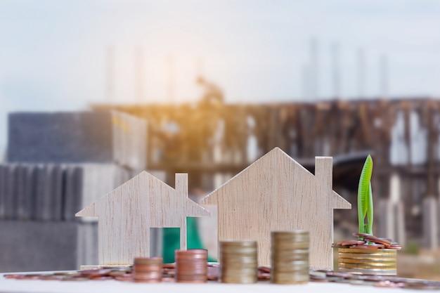 ぼやけた建設サイトの背景を持つ家モデルとお金コインスタックのクローズアップ Premium写真