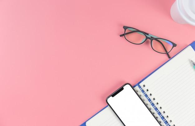 本とピンクのパステル調の背景にメガネのスマートフォン Premium写真