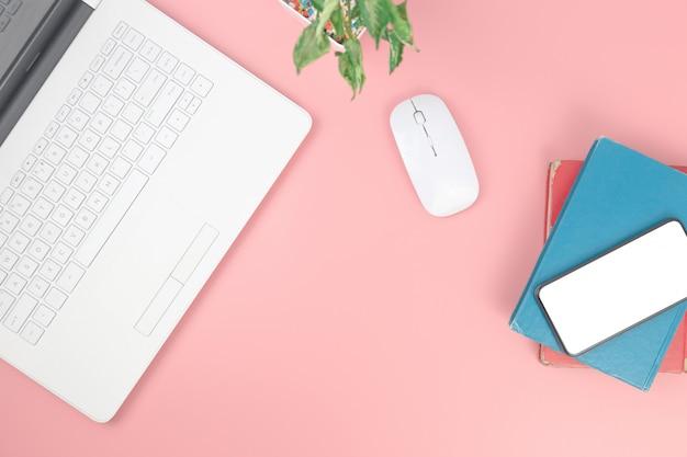 Вид сверху с ноутбука ноутбука смартфона на книги наверху на розовом фоне пастельных Premium Фотографии