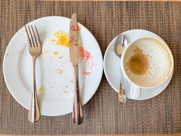 空の白い皿と木製のテーブルで朝食後コーヒーカップ。 Premium写真