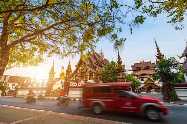 多くの赤いタクシーとチェンマイの夕方の寺院でにぎやかな通りへの旧市街の堀 Premium写真