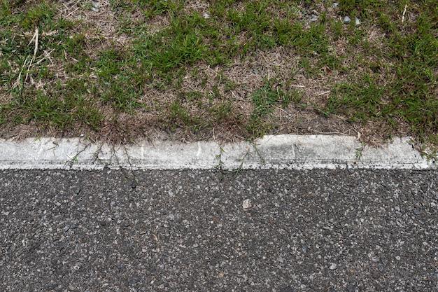 Дорога асфальта с нашивками и текстура зеленой травы предпосылка, пустой космос экземпляра. Premium Фотографии