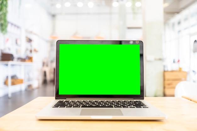 Макет изображение ноутбука с пустой зеленый экран на деревянный стол в кафе. Premium Фотографии